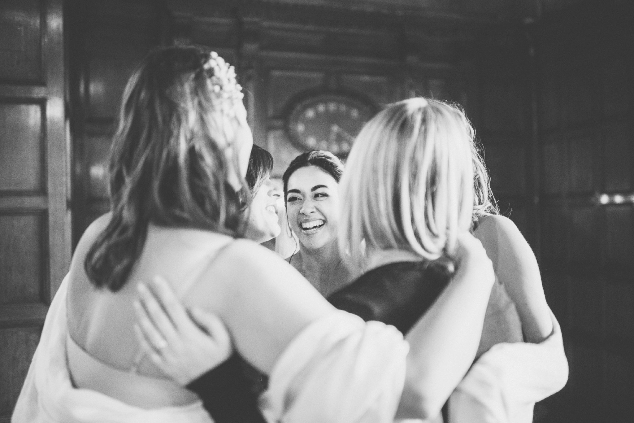 Bride hugging her bridesmaids at her Two Temple Place grand elegant London City Wedding