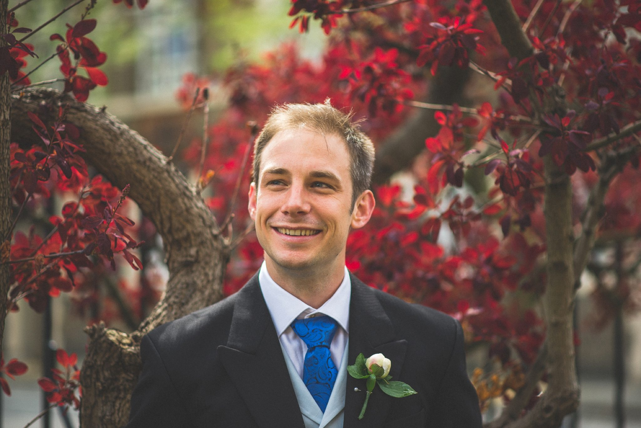 Groom standing in front of deep red foliage