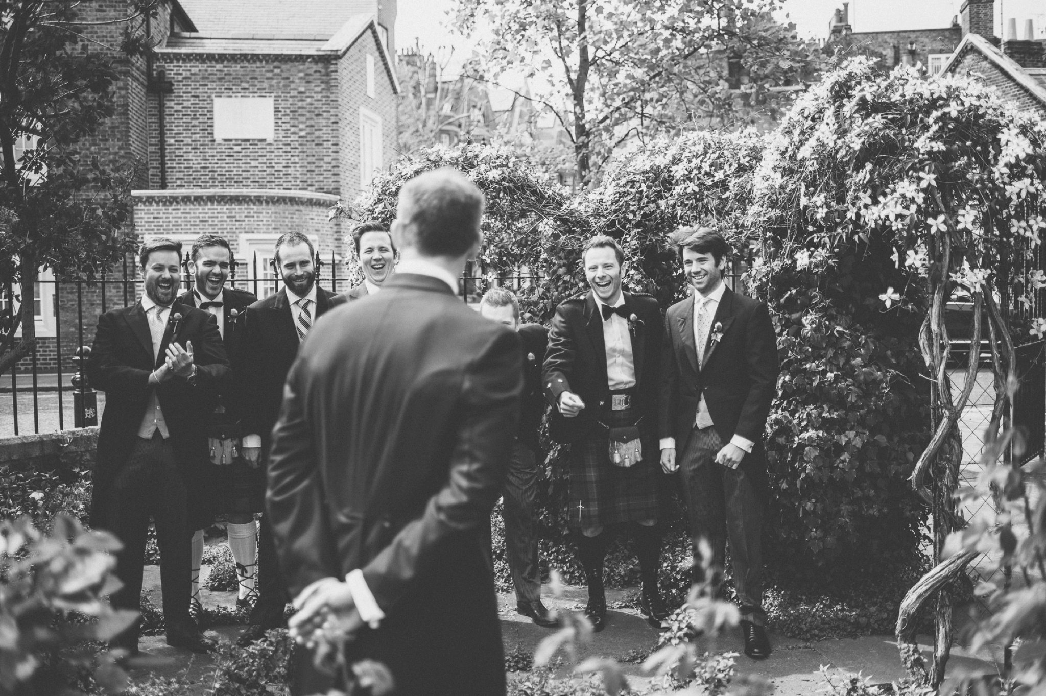 Groomsmen laughing and pointing at the groom