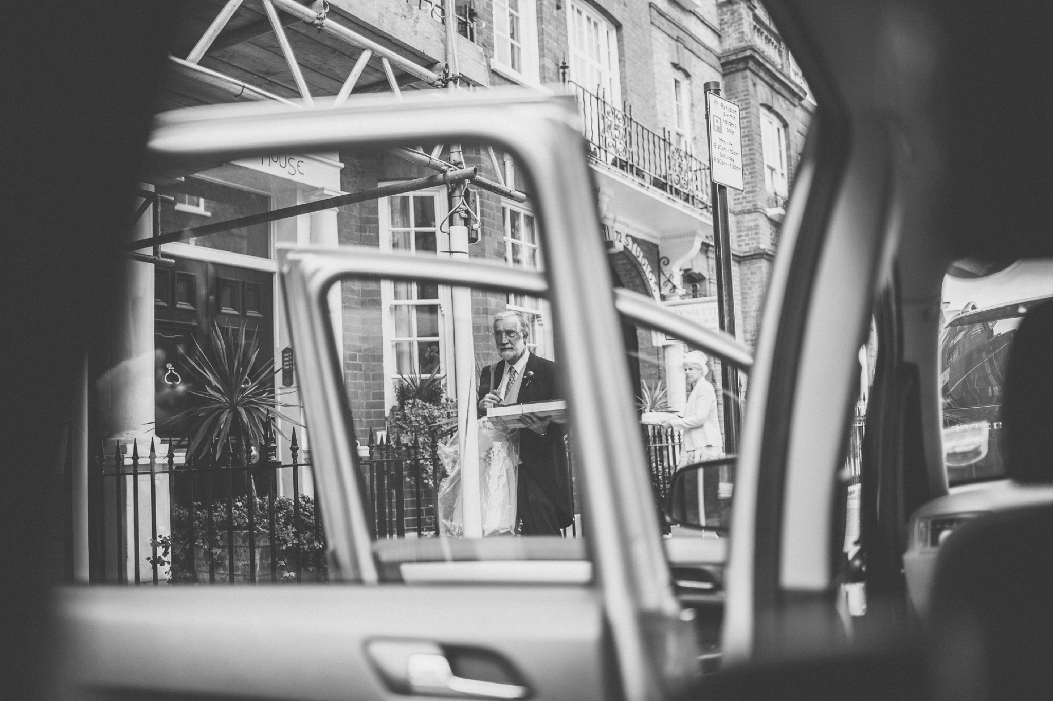 Groom's parents leaving for his Chelsea Wedding seen through the wedding car's windows