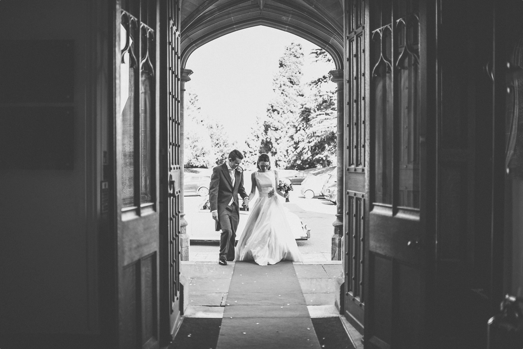 Bride and groom entering the huge gate for their sunbathed funfilled Horsley Towers autumn wedding