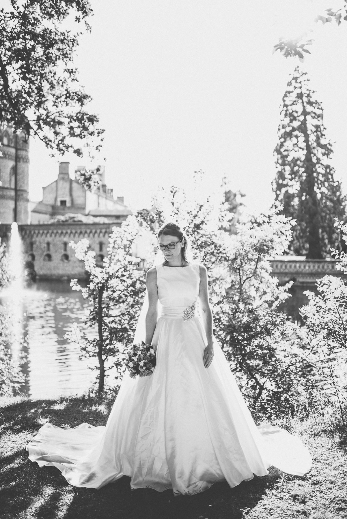 Sunlit bride standing by Horsley Towers lake at her autumn wedding