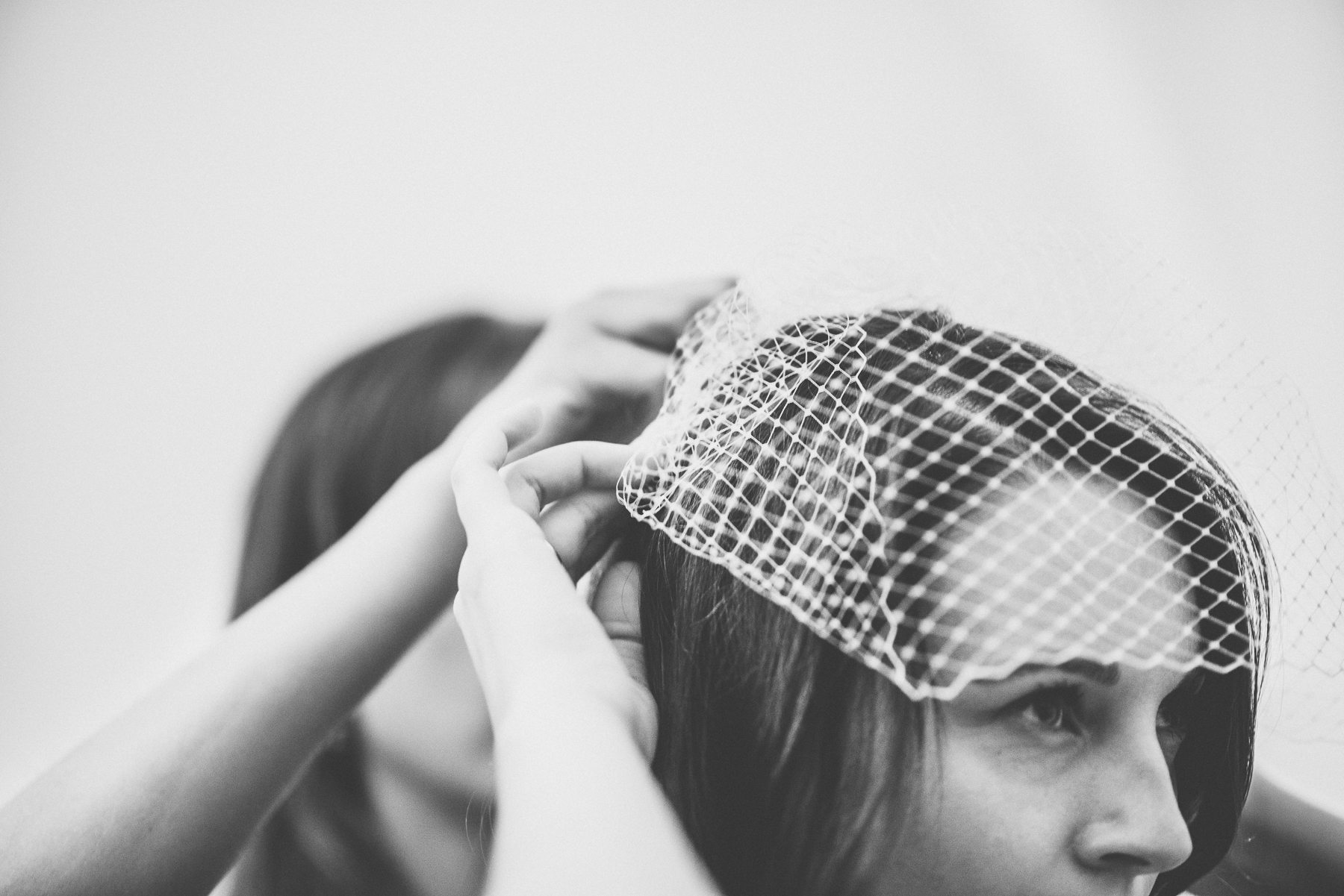 Bridesmaids putting on the bride's veil by best wedding photographer Maria Assia Photography