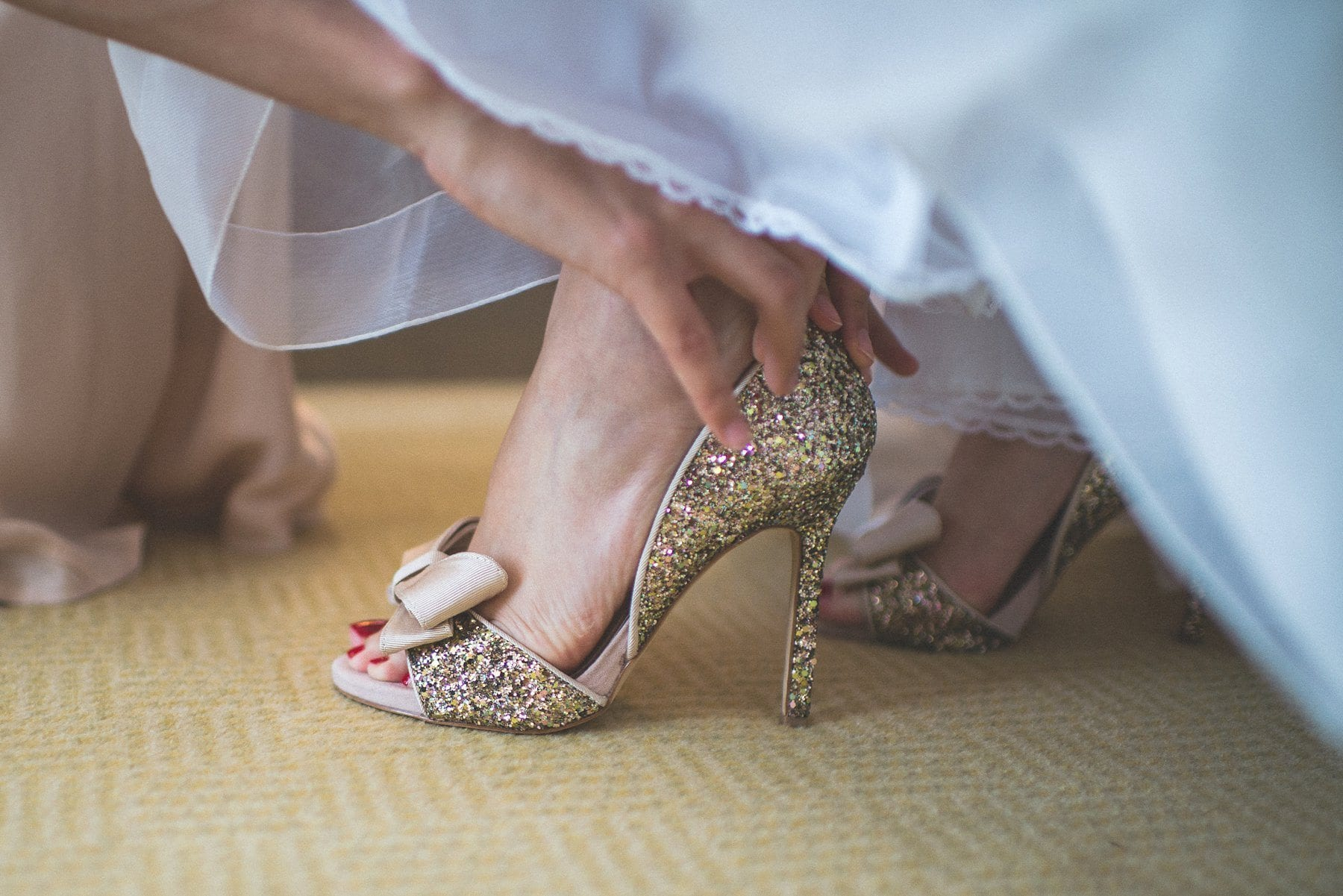 Bridesmaid putting on the bride's gold glitzy sparkly wedding shoes at the Chelsea Harbour Hotel wedding