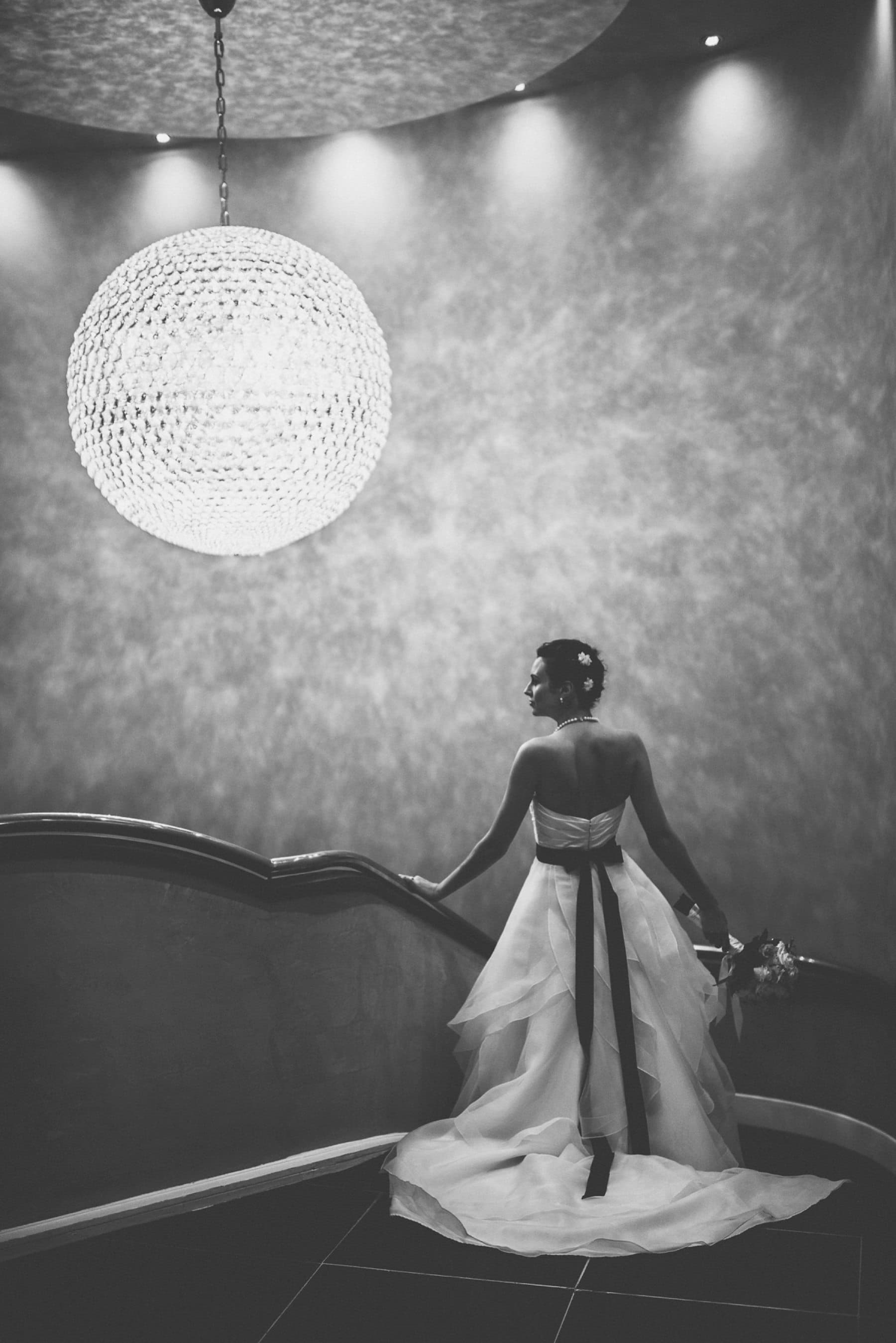 Glamorous Bride standing under the Chelsea Harbour Hotel chandelier on her way to her Hurlingham Club Glamorous Music Themed Wedding