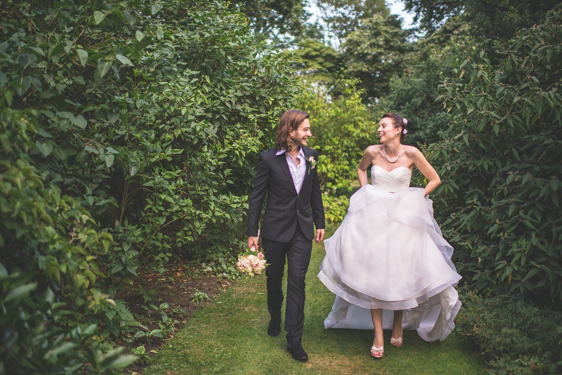Bride and groom walking through the grounds at Chelsea's Hurlingham Club
