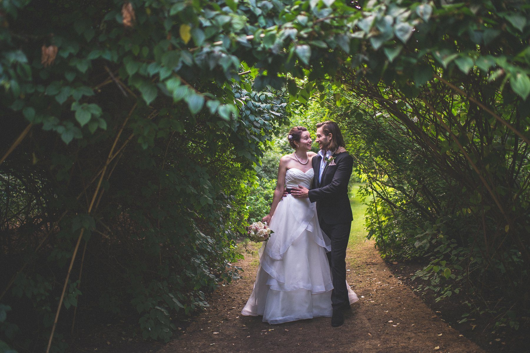 Bride and groom grinning at each other under a vine arch at Chelsea's Hurlingham Club