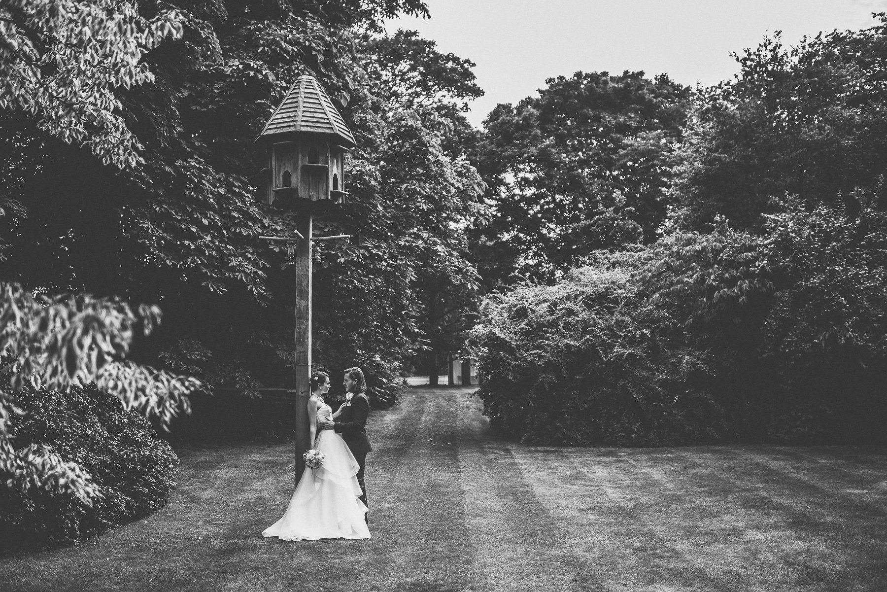 Bride and groom leaning against the bird house at their Glamorous wedding at Hurlingham Club in Chelsea London