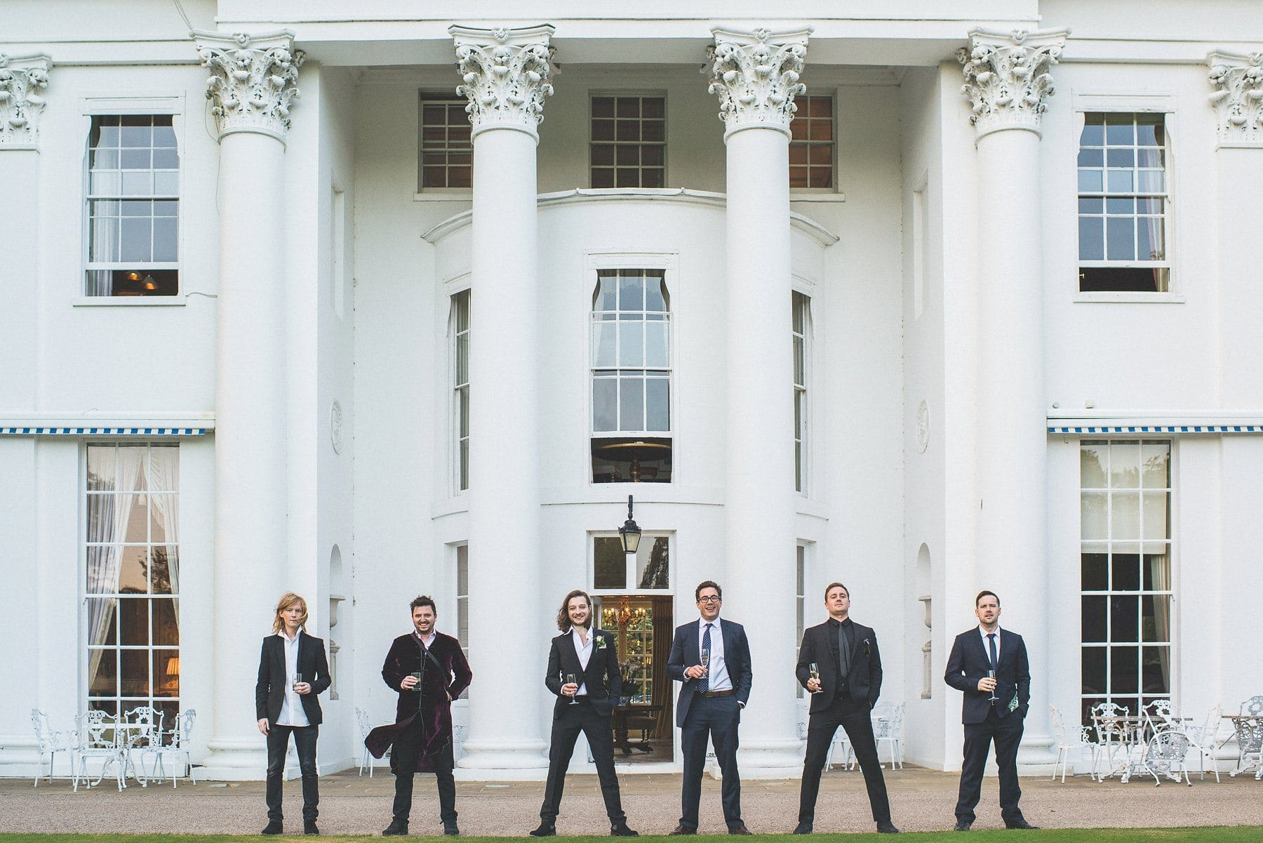 Groom and groomsmen standing in front of the white marble columns at the Hurlingham Club wedding