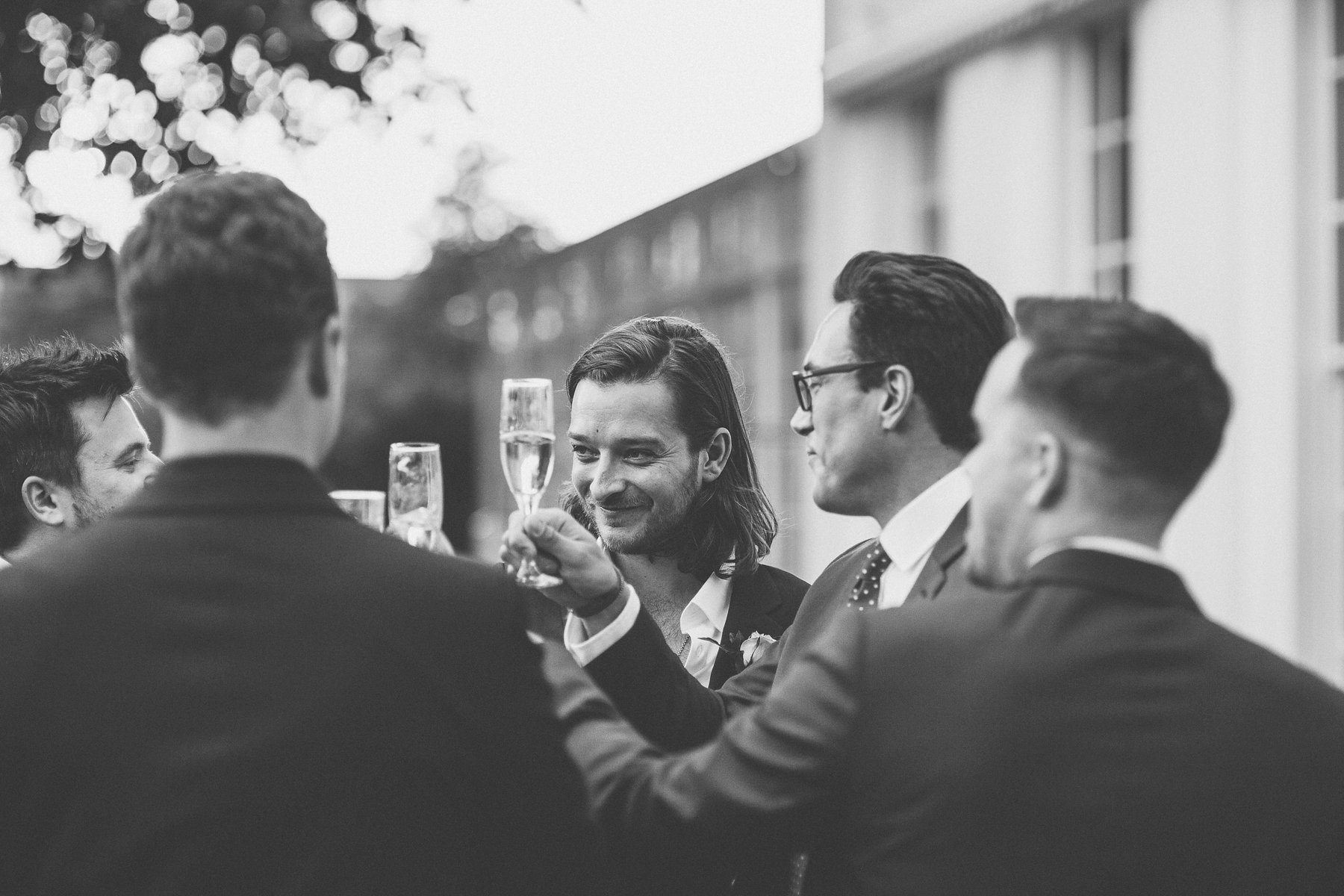 Groom and groomsmen toasting in the Hurlingham Club wedding grounds