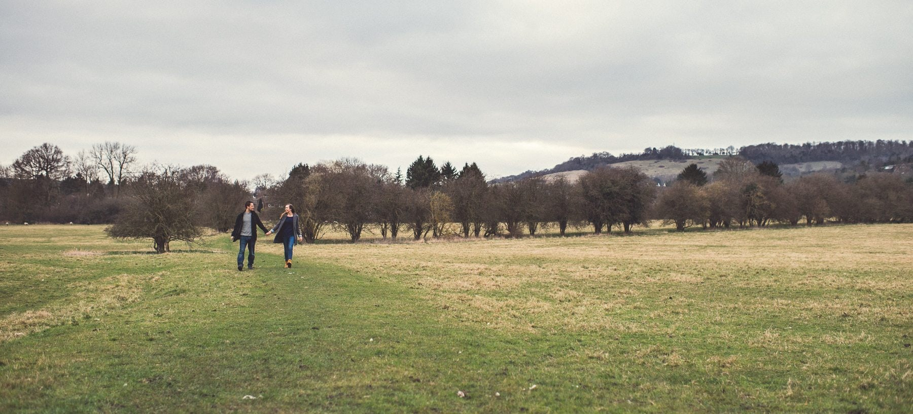Couple walking through the Kent Downs in front of St Julians Club