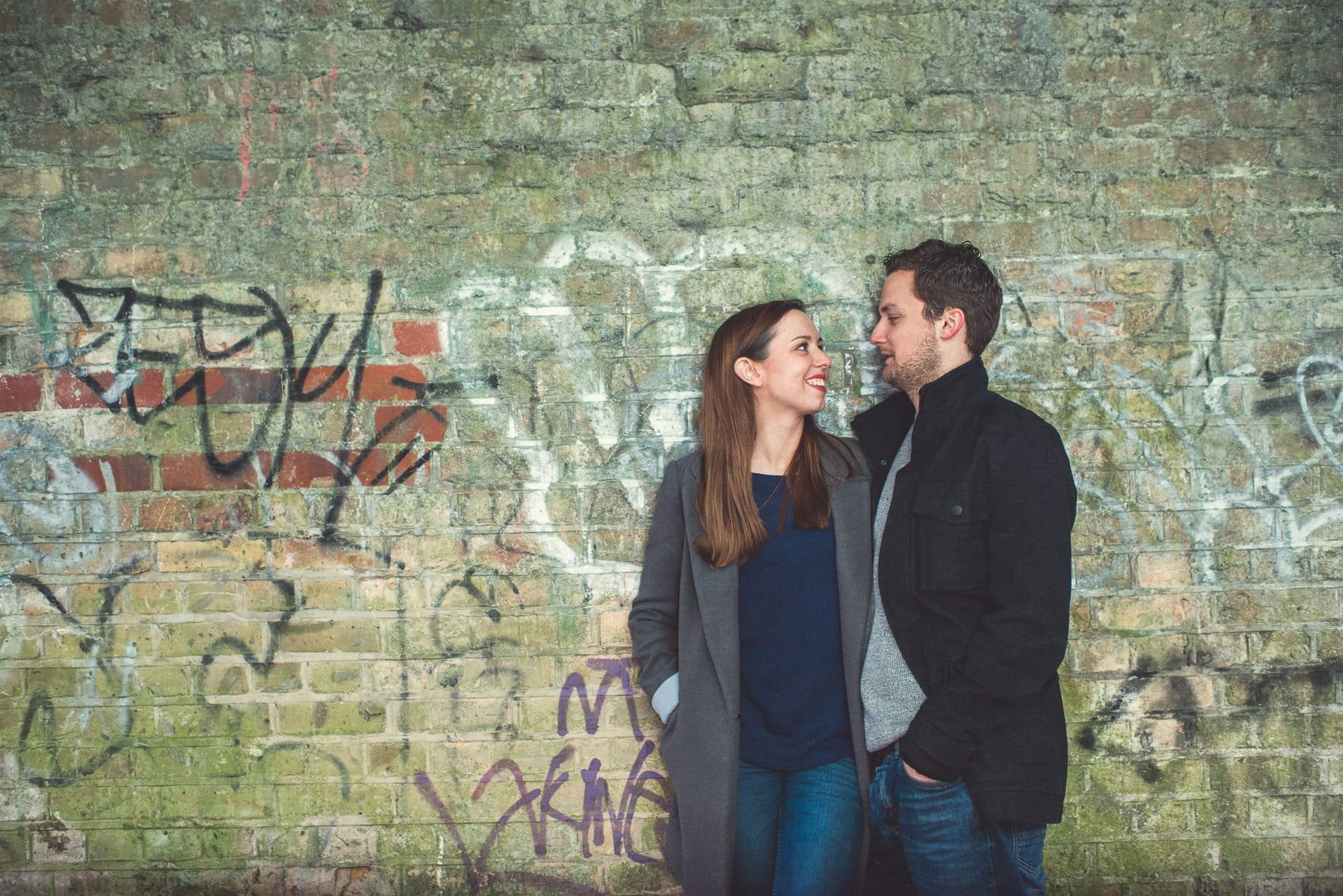 Couple standing under a graffiti covered brick tunnel on their romantic relaxed engagement shoot