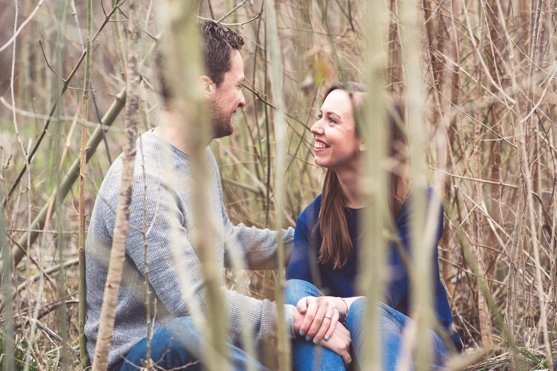 Couple sitting and smiling at each other in a bunch of bamboo and twigs by Kent wedding photographer Maria Assia Photography