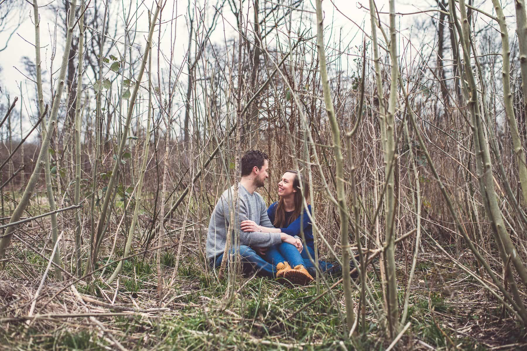 Kent Downs romantic relaxed engagement shoot couple sitting in a field of bamboo twigs by winter wedding photographer Maria Assia Photography