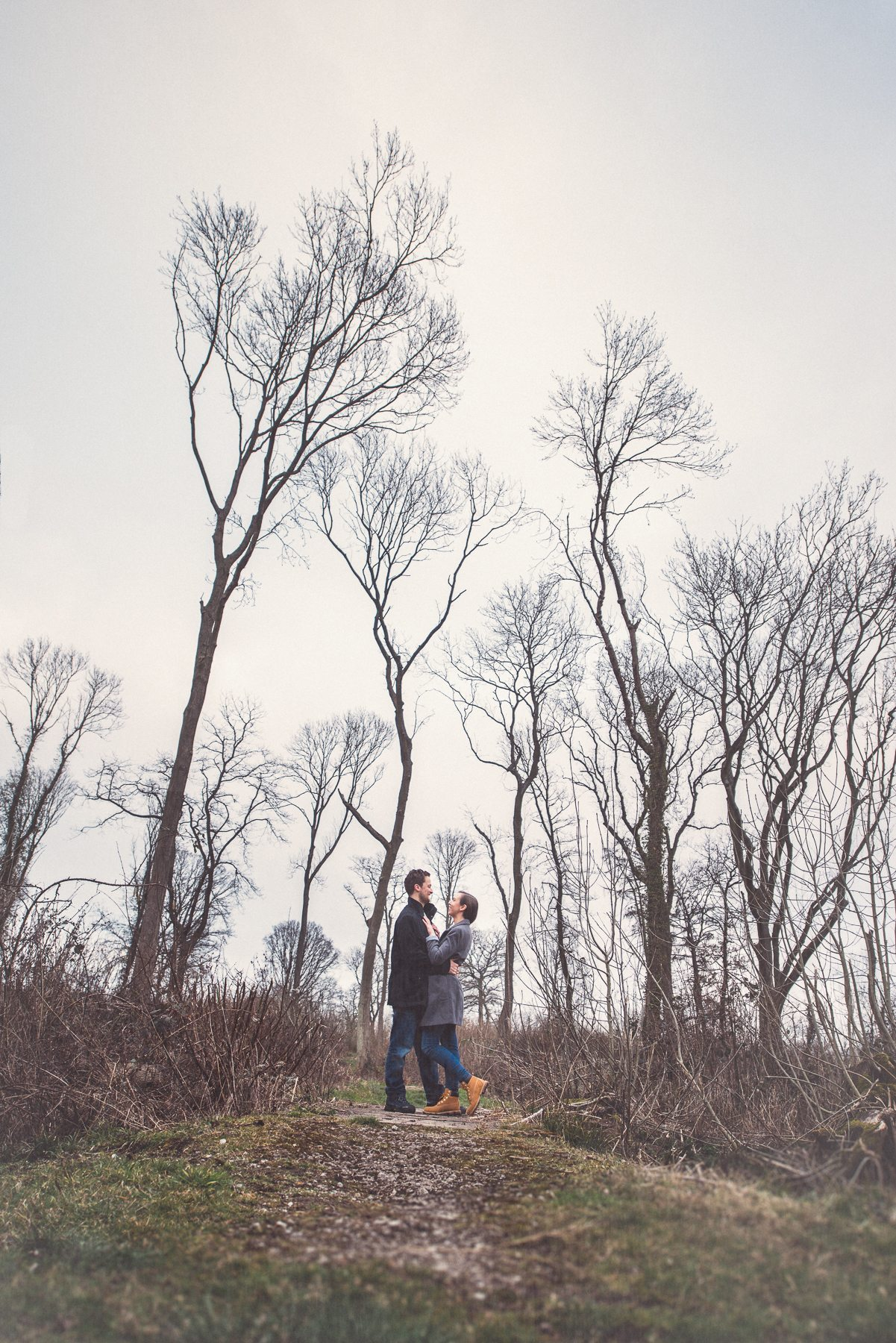 Engaged couple standing in the woods in Sevenoaks Kent overlooking the Kent Downs and St Julians Club