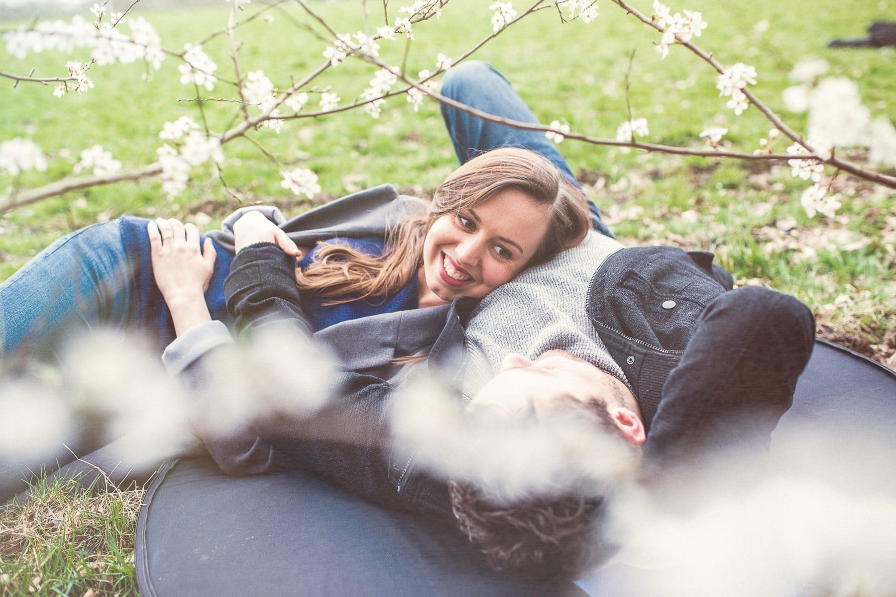 Couple lying and smiling at each other surrounded by cherry blossoms