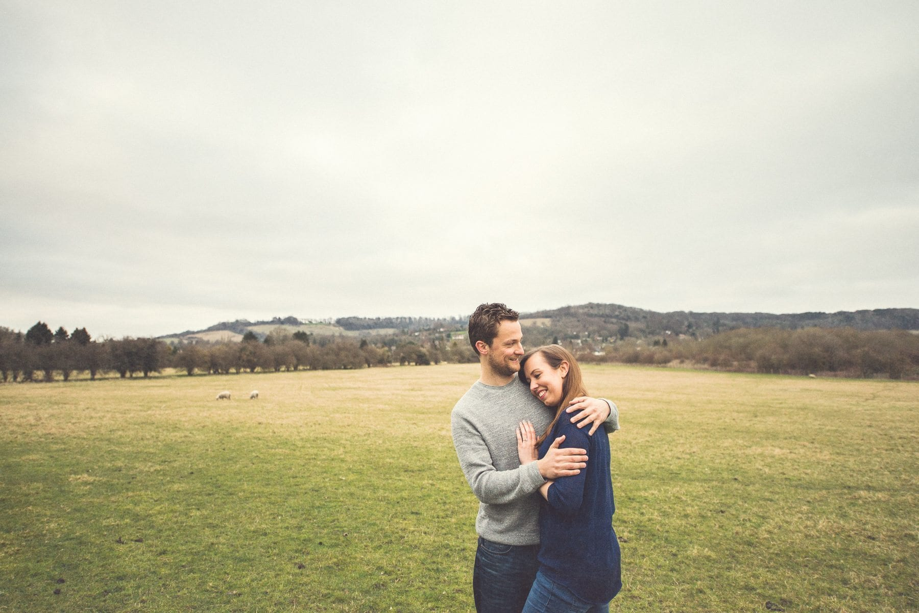 Couple hugging in a field in front of St Julians Club overlooking the Kent Downs