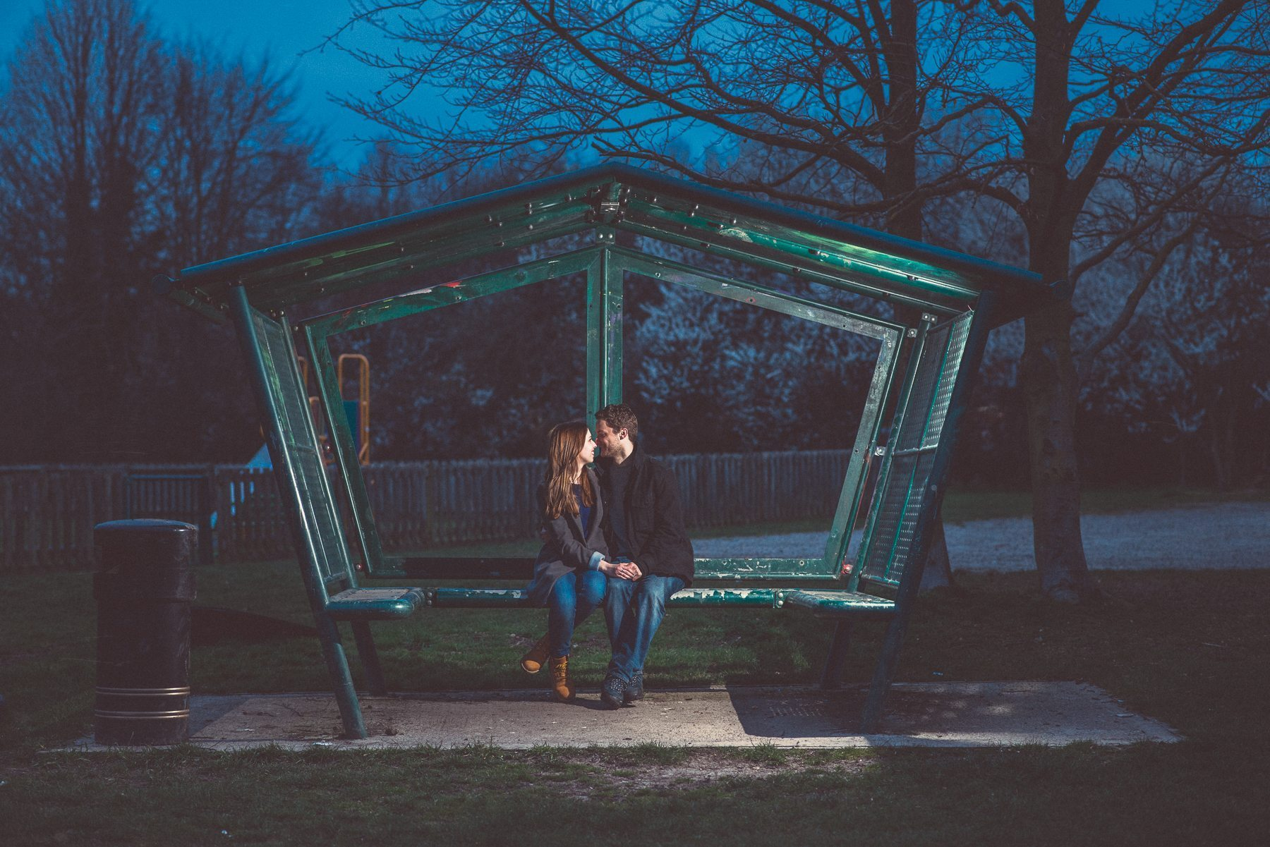 Romantic relaxed engagement shoot of a couple sitting on a bench in a park in the Kent Downs
