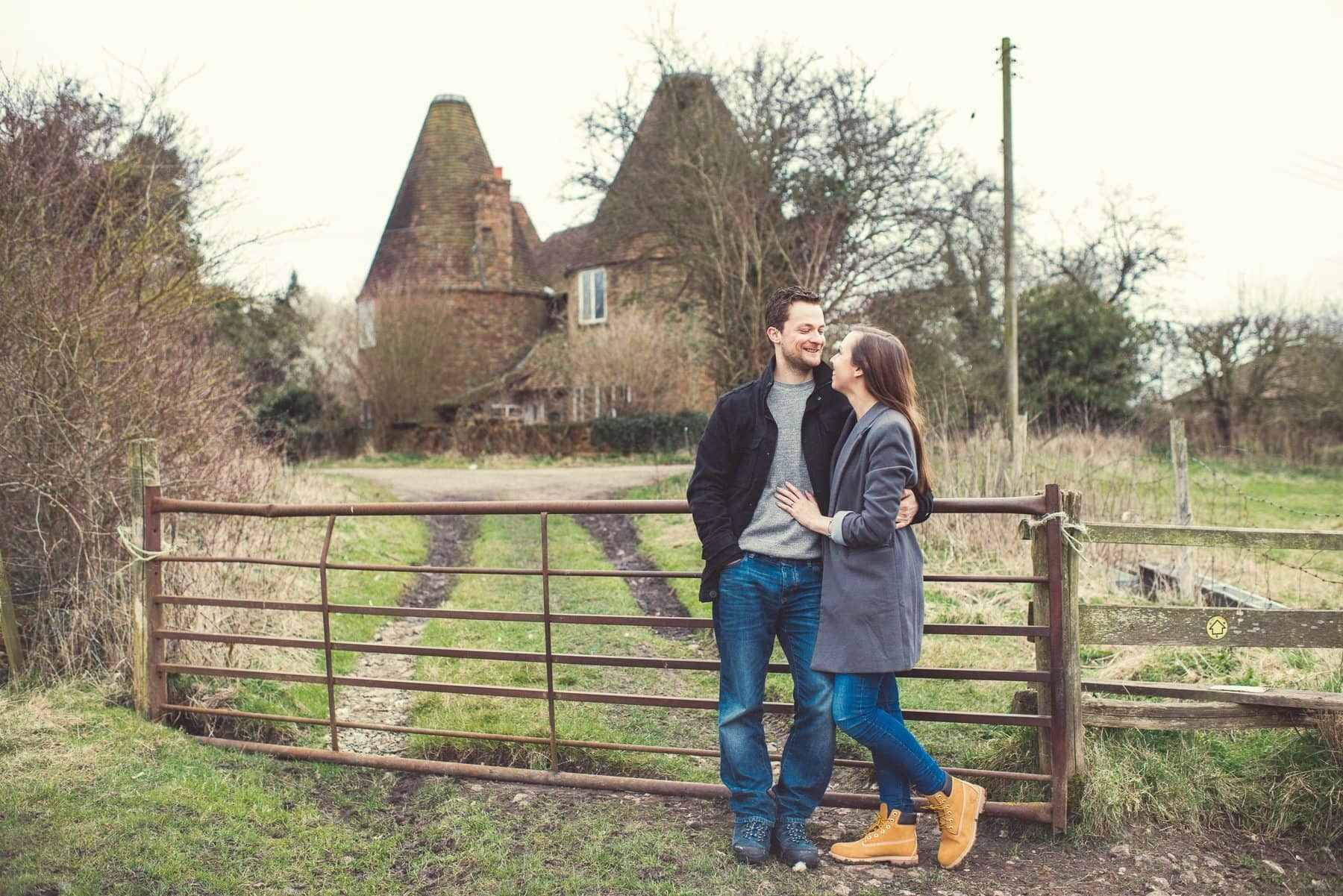 Kent Downs engagement shoot with a couple standing in front of two Oast Houses overlooking St Julians Club