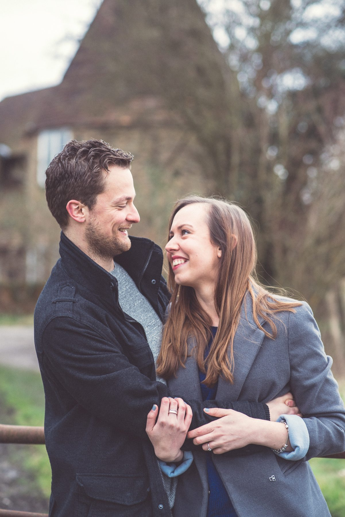 Engaged Couple looking at each other in front of an Oast House overlooking St Julians Club in Sevenoaks