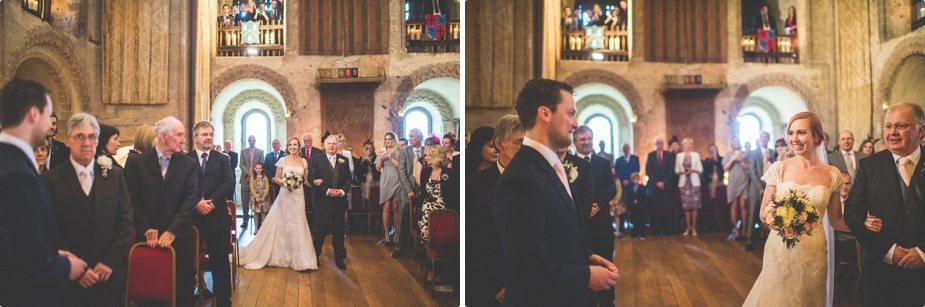 Bride walking into her candle lit wedding ceremony at Hedingham Castle