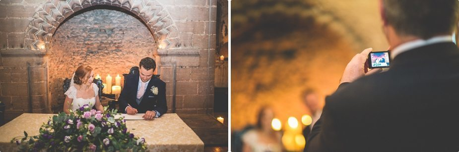 Bride and groom signing the register at their candle lit Hedingham Castle wedding
