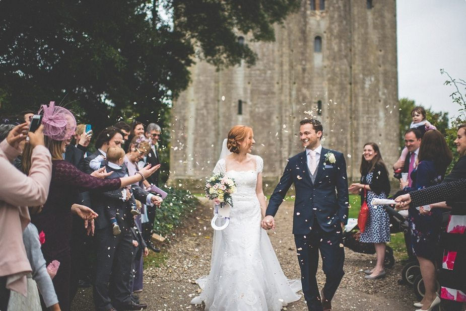 Bride and groom walking through their confetti shower at Hedingham Castle