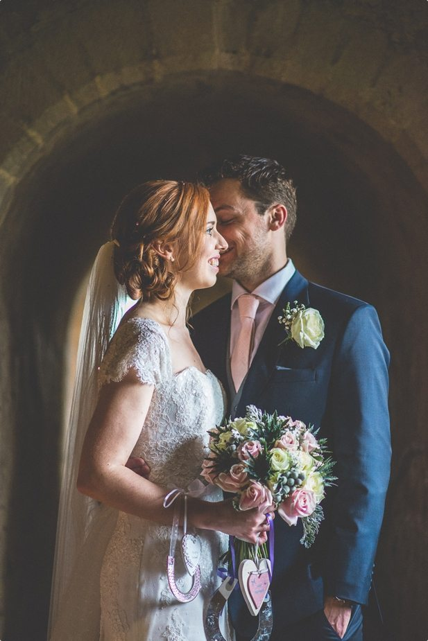 Bride and groom standing in a light beam at their Hedingham Castle Wedding