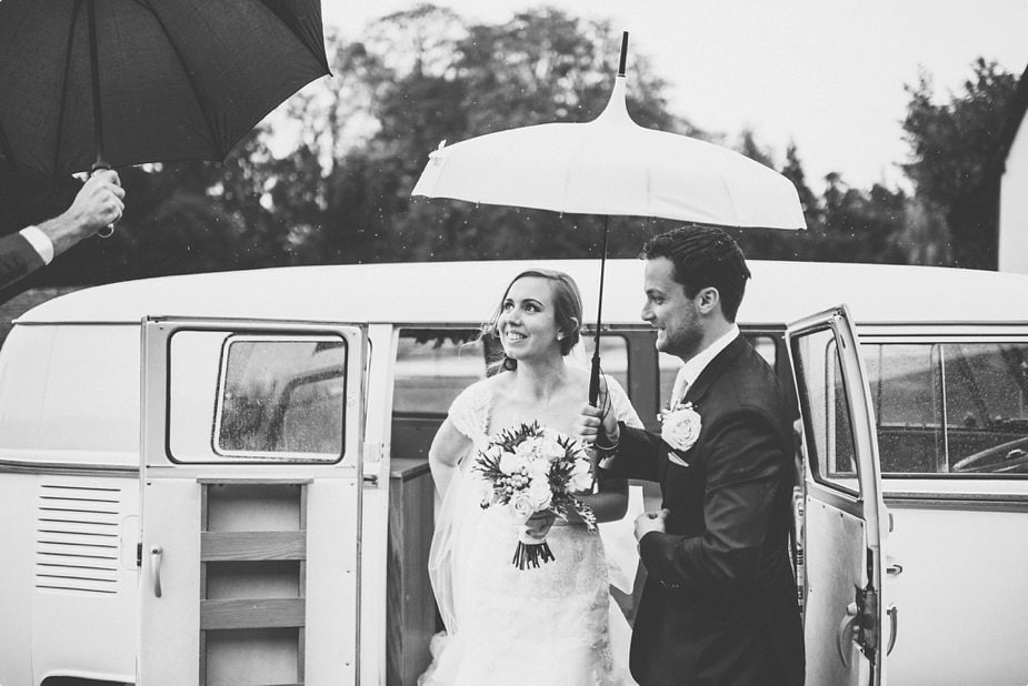 Bride and groom arriving in their VW van at their Smeetham Hall Barn rustic rainy wedding