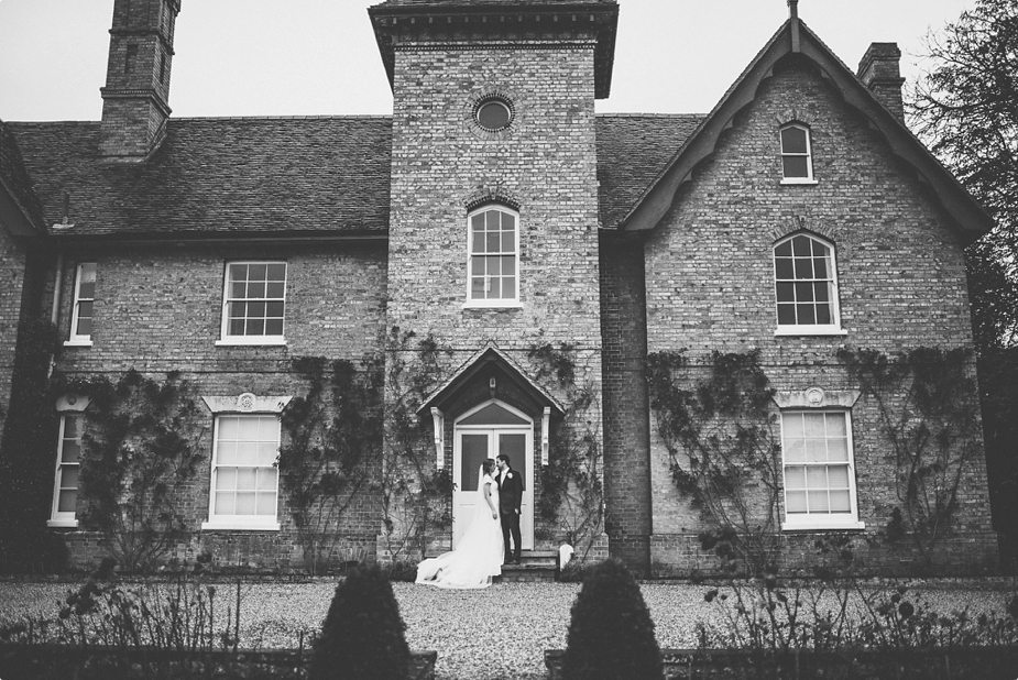 Bride and groom standing in front of Smeetham Hall Barn Manor House at their rustic rainy wedding