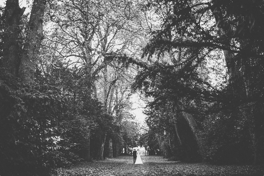 Bride and groom walking under their umbrella through the autumn leafy alley at their smeetham hall barn rustic rainy wedding
