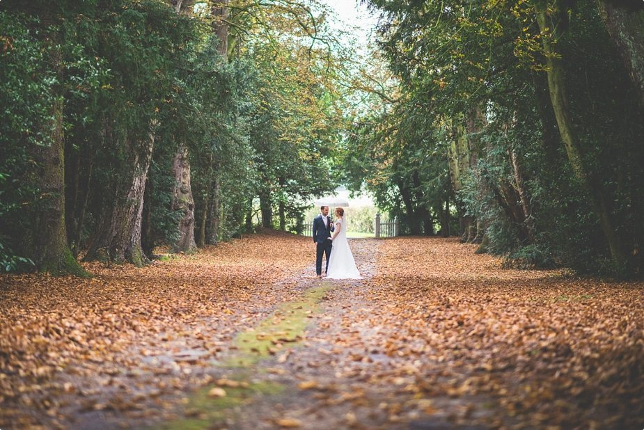 Smeetham Hall Barn wedding bride and groom standing in the autumn leaves