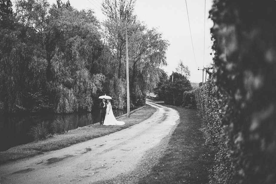 Bride and groom standing in the rain at their wedding at Smeetham Hall Barn lake