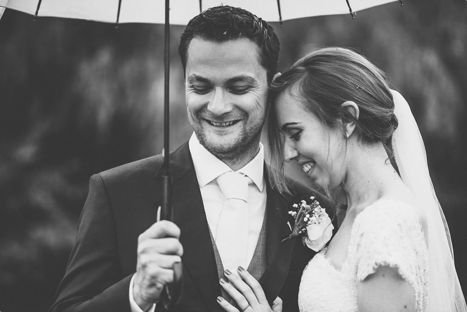 Bride and groom laughing in the rain under their umbrella at their Smeetham Hall Barn rustic rainy wedding