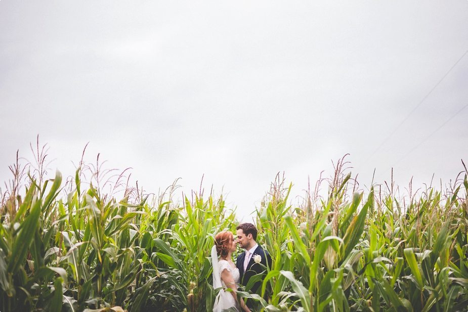 Bride and groom surrounded by a foggy cornfield at their Smeetham Hall Barn rustic rainy wedding