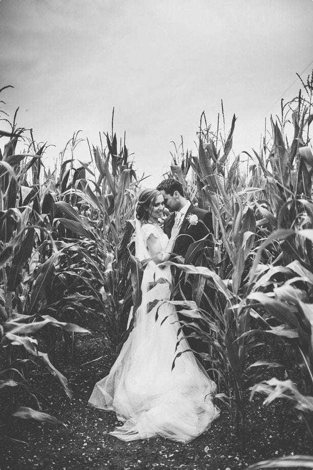 Bride and groom hugging closely in a cornfield at Smeetham Hall Barn