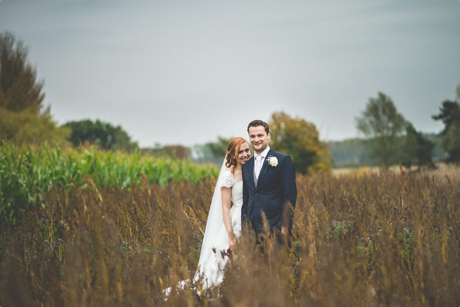 Bride and groom standing in the field at their Smeetham Hall Barn rustic rainy wedding
