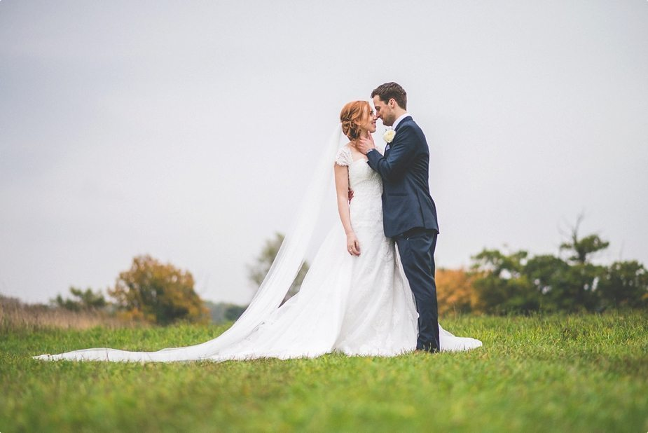Smeetham Hall Barn rustic rainy wedding Bride and groom hugging in the field with the bride's wedding dress and wedding veil trailing behind her