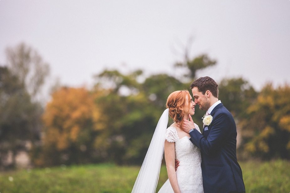Bride and groom standing close in the fields at their Smeetham Hall Barn rustic rainy wedding