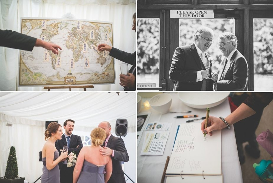 Wedding guests laughing, pointing at a world map seating plan and leaving messages to the bride and groom at their Smeetham Hall Barn rustic rainy wedding