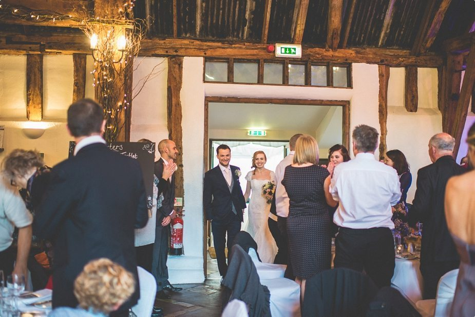 Bride and groom walking into the main hall at their Smeetham Hall Barn rustic rainy wedding