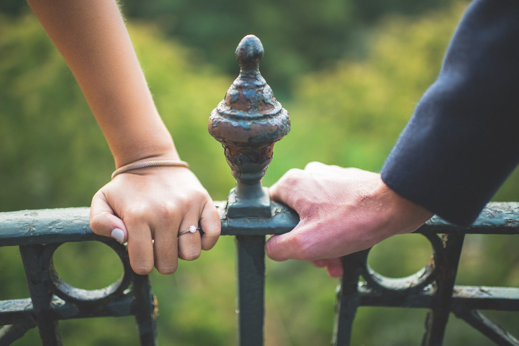 Engaged couple's hands holding on closely to a railing