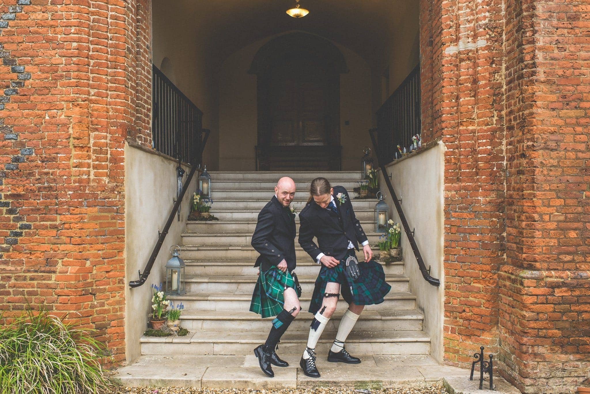 Scottish Groom and best man showing off their legs under their kilts at Farnham Castle