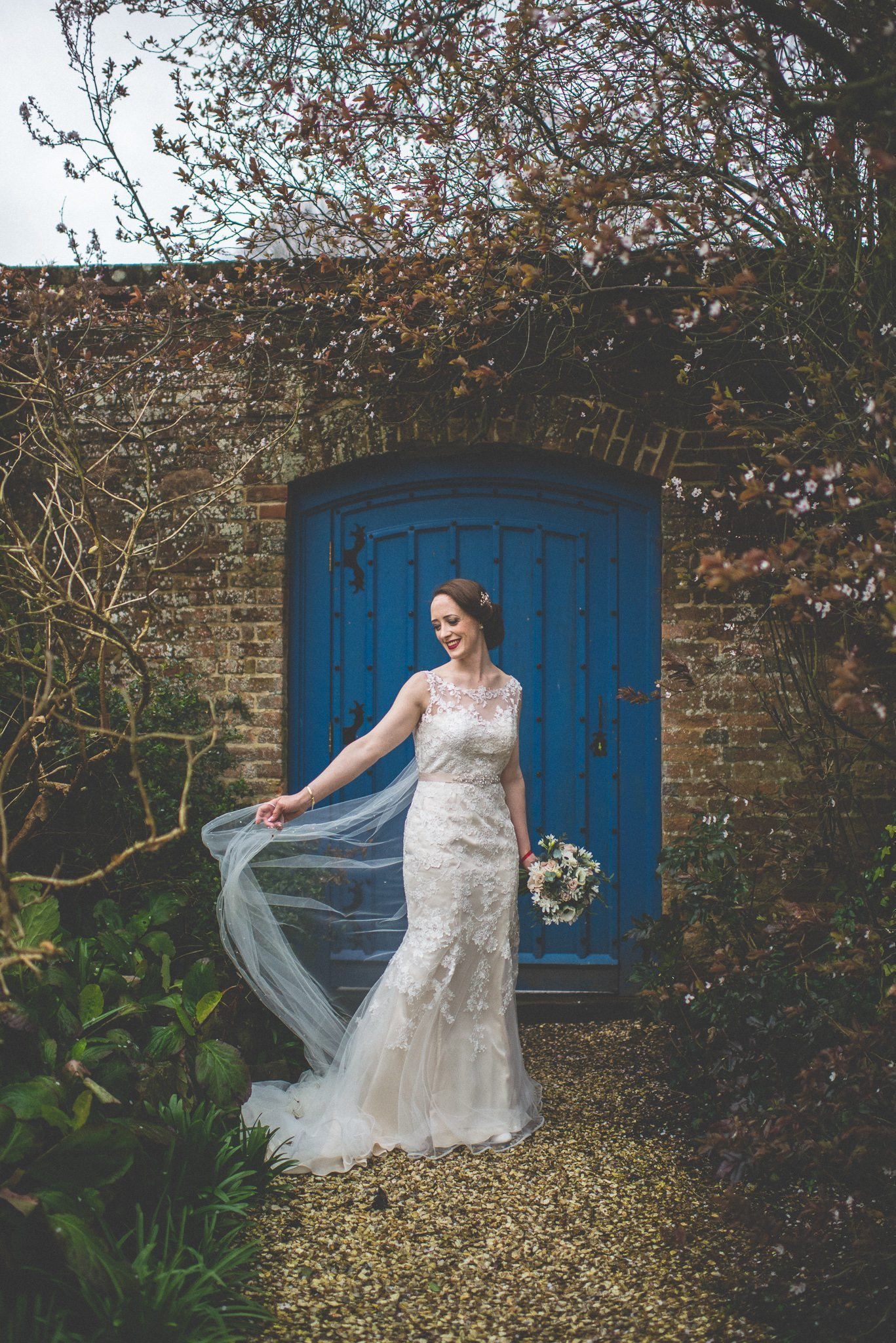 Bride holds her windswept veil at Farnham Castle