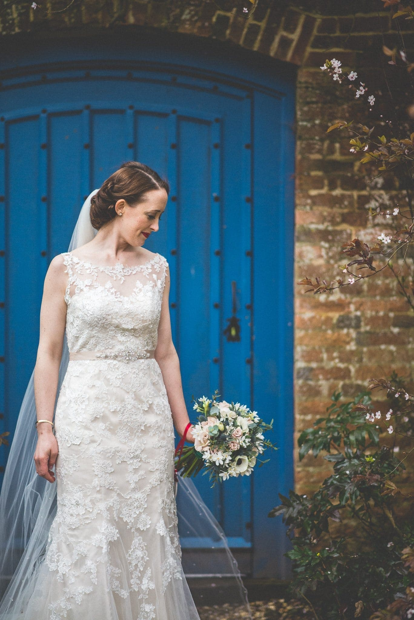 Bride looking at her bouquet before walking to her wedding ceremony at Farnham Castle
