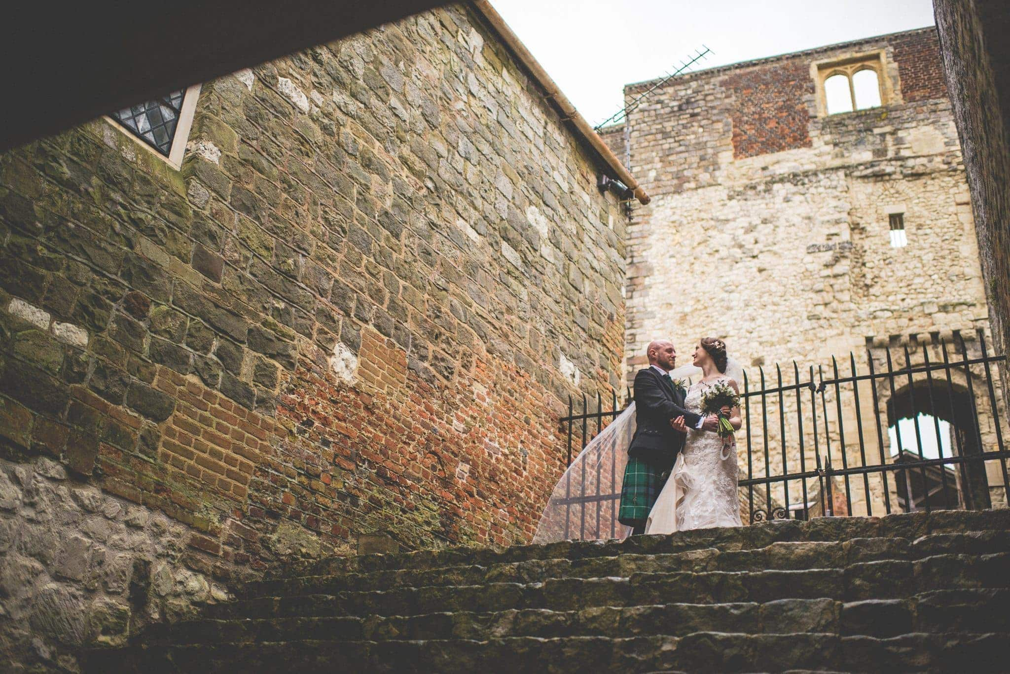 Bride and Groom laugh at each other at the steps of the Keep at Farnham Castles