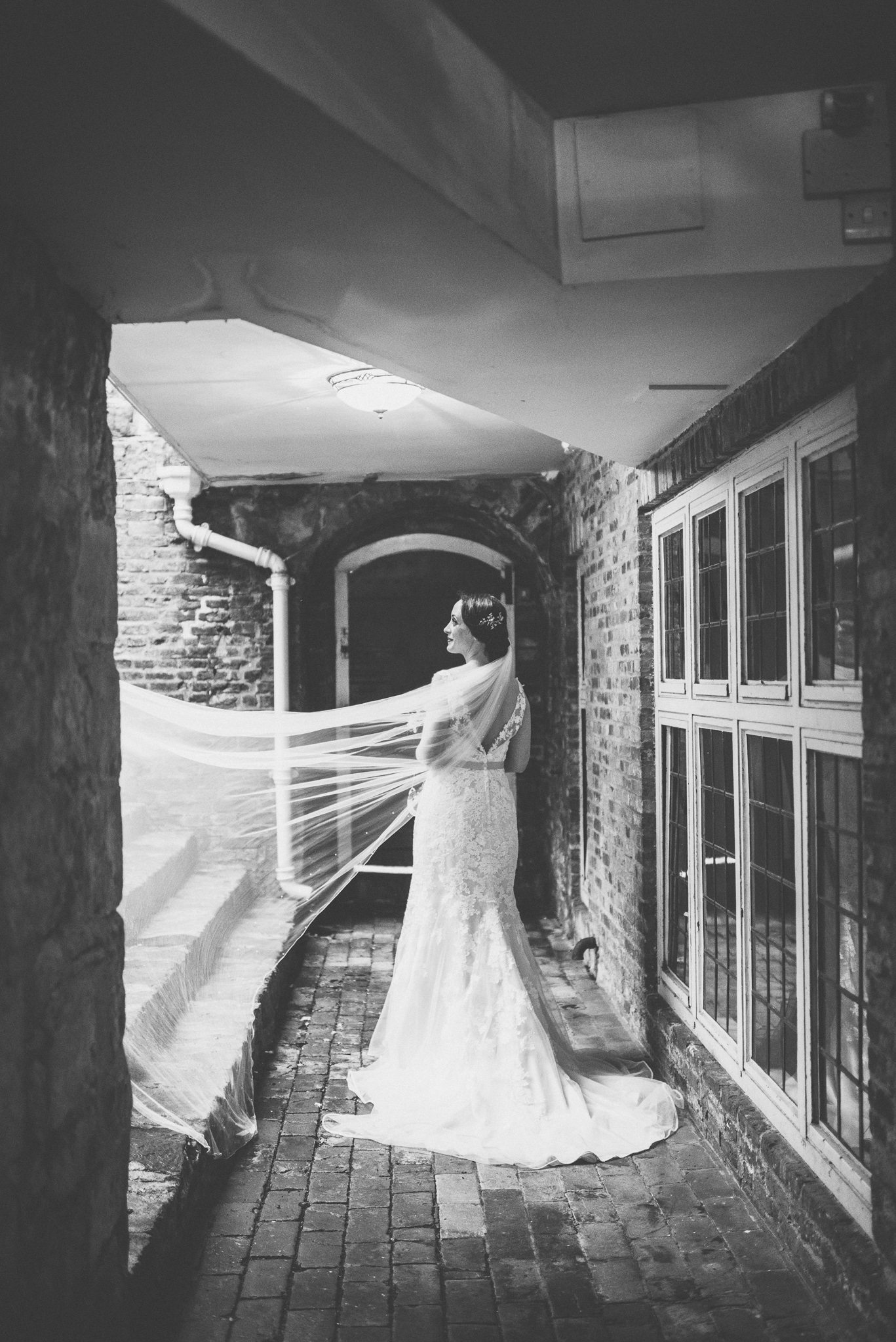 Bride looking on as her wedding veil is blown up the stairs creative photography by maria assia photography Farnham Castle Wedding Photography