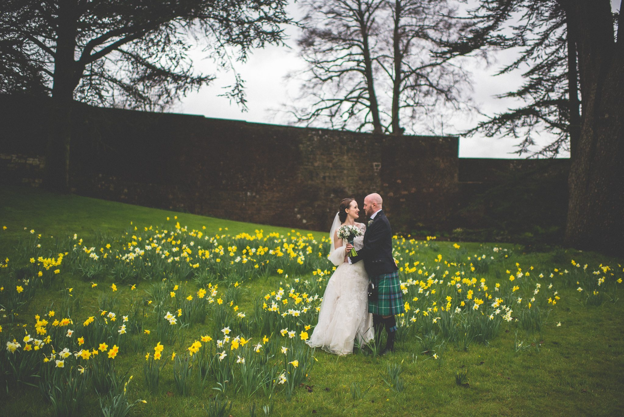 Scottish Bride and Groom stand surrounded by Daffodils in the grounds of Farnham Castle