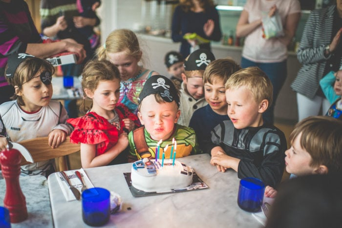 Boy blowing out his birthday cake candles surrounded by his friends by Maria Assia Photography