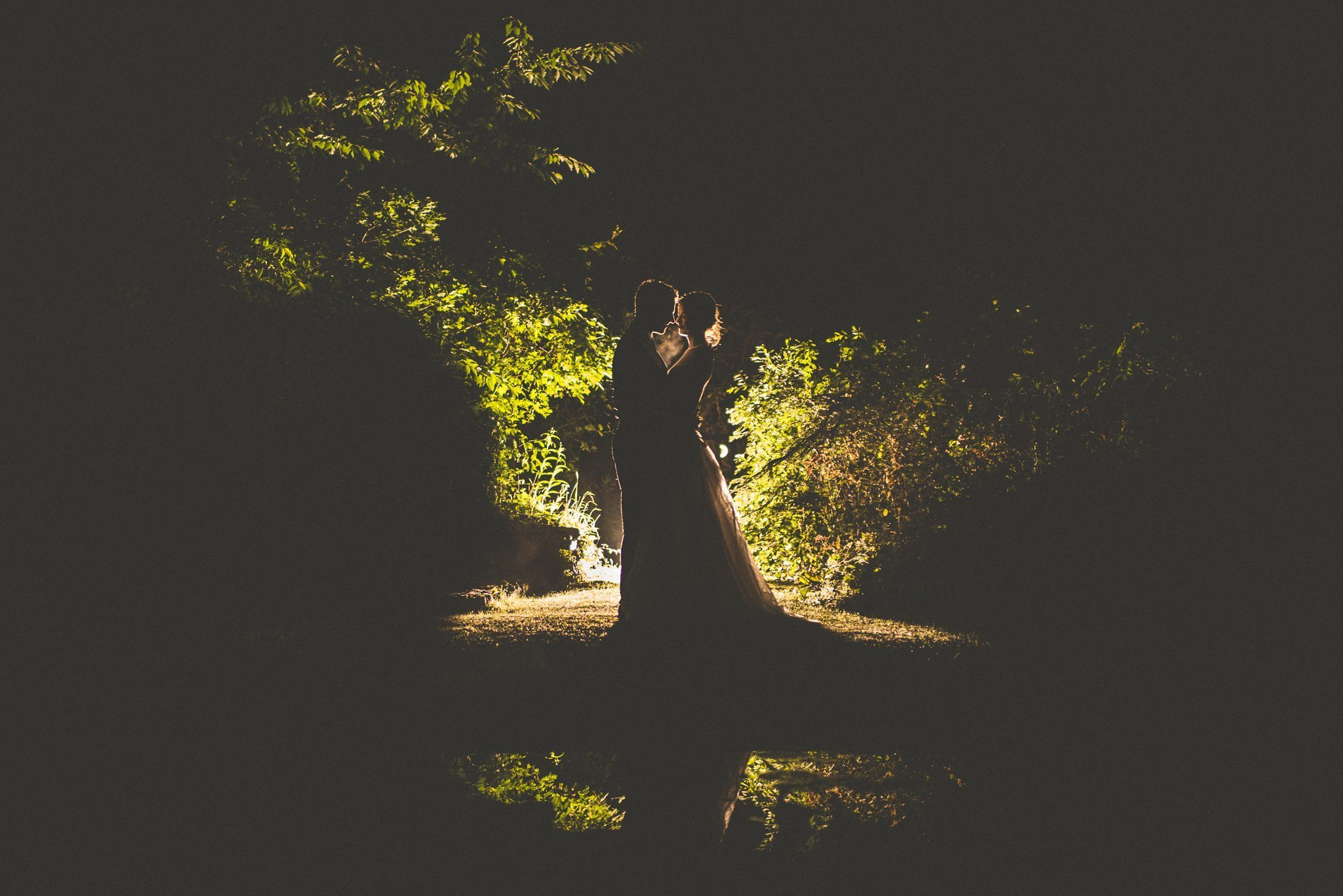Bride and groom creative evening shot with a lake reflection by Maria Assia Photography